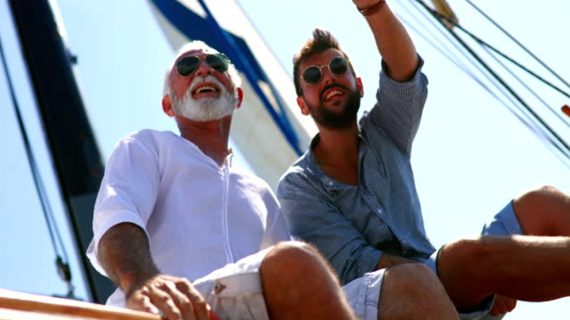 Father and son sailing. Closeup low angle view of mid 60's man and his son enjoying summer holiday on a sailboat. They are sitting on the deck, looking at the distance, talking and laughing. handsome people stock videos & royalty-free footage