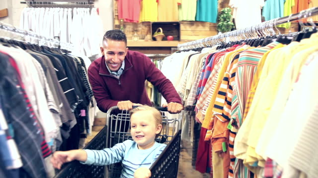 father and son shopping for clothing, playing with cart - 30 34 anni video stock e b–roll