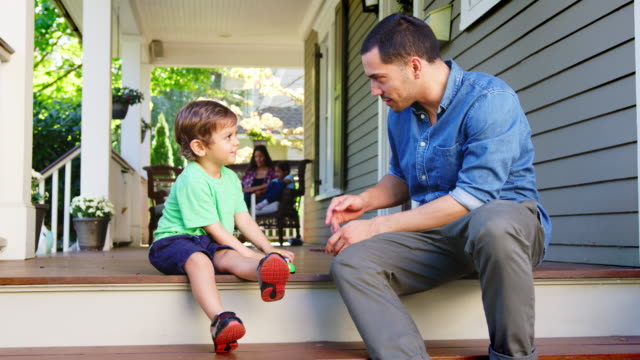 Father And Son Sit On Porch Of House Playing With Toys Together Father And Son Sit On Porch Of House Playing With Toys Together porch stock videos & royalty-free footage