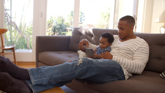 Father And Son Sitting On Sofa At Home Using Digital Tablet video