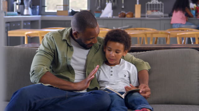 Father And Son Sitting On Sofa Looking At Counting Book Together video