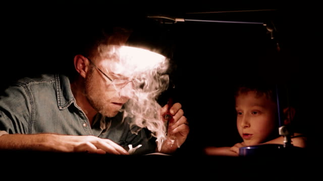 Vater und Sohn sitzen zusammen unter Lampe am Tisch mit Lötkolben, um einige elektronische Geräte zu reparieren und zu sprechen – Video