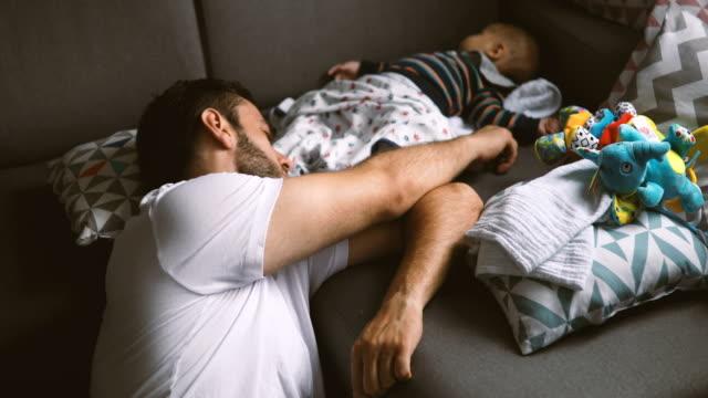 Padre e hijo durmiendo en el sofá - vídeo
