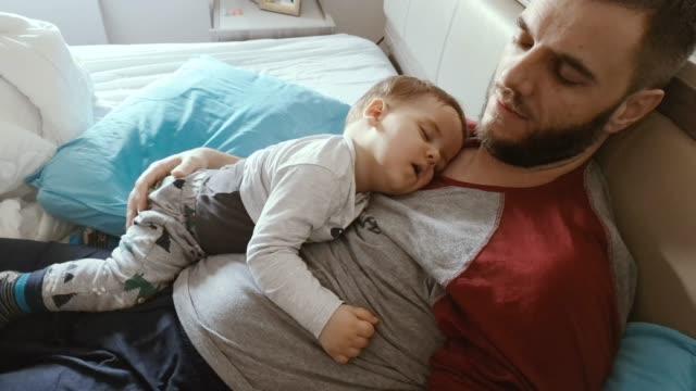 father and son sleeping - syn filmów i materiałów b-roll
