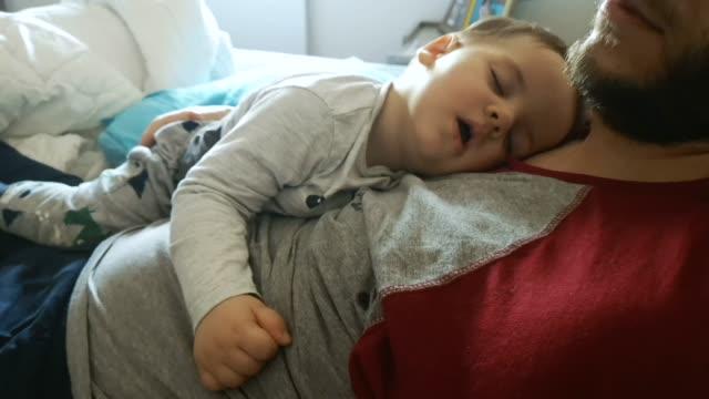 vídeos y material grabado en eventos de stock de padre e hijo durmiendo - desordenado