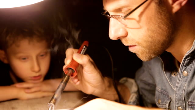 Father and son solder electrical parts under the table lamp video