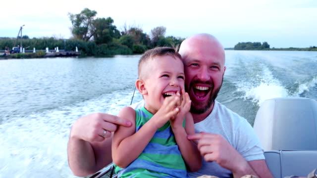Pai e filho passar tempo juntos, emocionalmente responder durante a condução rápida em um barco de alta velocidade, uma família em férias de verão, um bom pai no fim de semana com a criança - vídeo