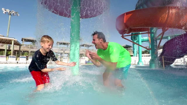Father and son splashing each other at water park video