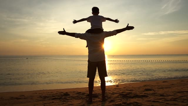 father and son standing on the beach at sunrise, they spend quality family time together. shooting with slow-motion camera. - padre single video stock e b–roll