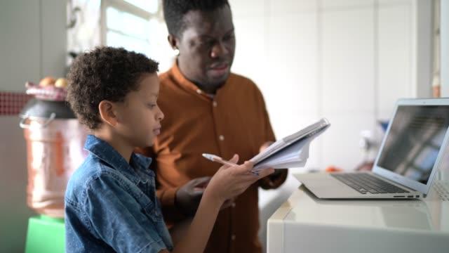 baba ve oğlu evde bir online sınıfta dizüstü bilgisayar ile eğitim - dijital yerli stok videoları ve detay görüntü çekimi