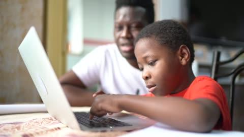 padre e figlio che studiano con il laptop in una lezione online a casa - imparare video stock e b–roll