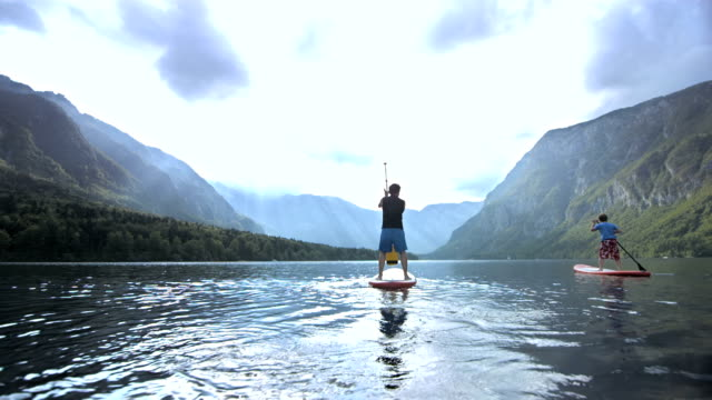 Father And Son SUPing On The Lake HD1080p: Slow Motion shot of a young father and his son stand up paddle surfing on the lake. holidays stock videos & royalty-free footage