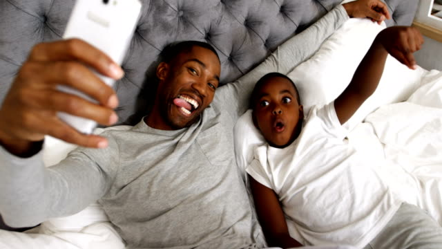 vídeos de stock e filmes b-roll de father and son taking selfie with mobile phone in bedroom 4k - confortável