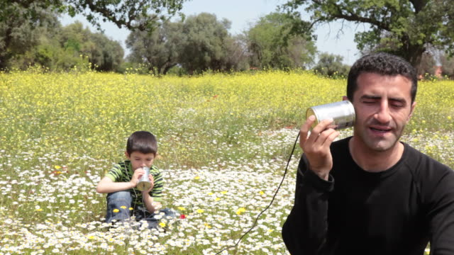 Father and son talking on can phone video