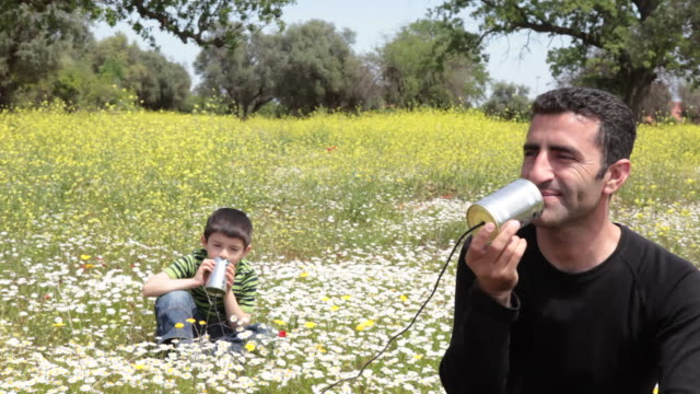 Father and son talking on can phone