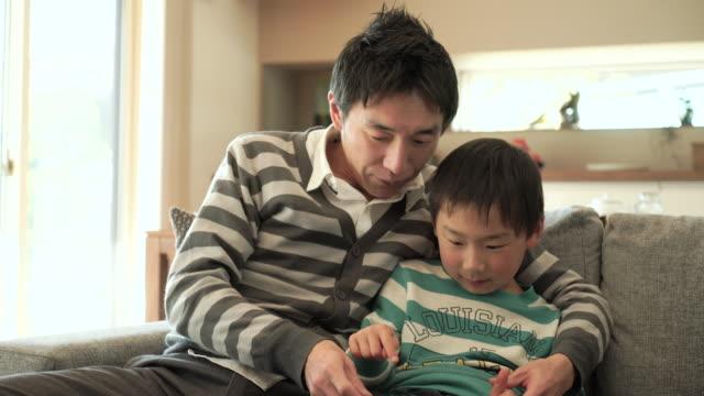 父と息子デジタルタブレットを使用したシッティングエリアのソファーベッド - パソコン 日本人点の映像素材/bロール