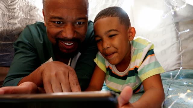 far och son med digital tablett i sovrum 4k - digital reading child bildbanksvideor och videomaterial från bakom kulisserna