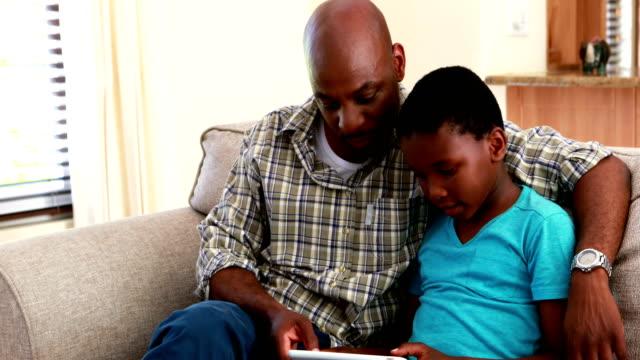 far och son med digital tablett i vardagsrummet 4k - digital reading child bildbanksvideor och videomaterial från bakom kulisserna