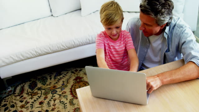 Father and son using laptop in living room 4k video