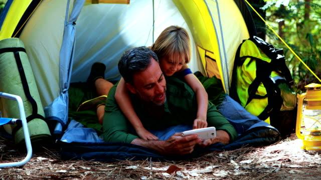 父と息子がテントの外で携帯電話を使用して - 息子点の映像素材/bロール