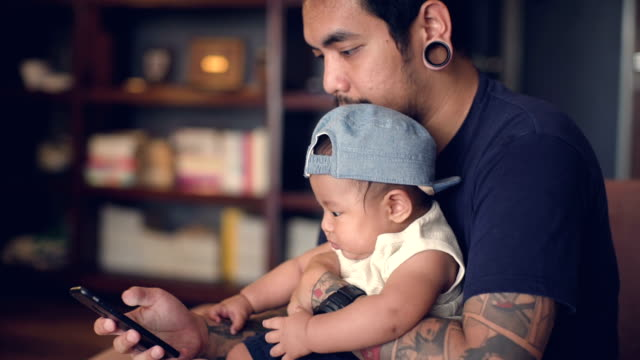 Father and son using smart phone at home video