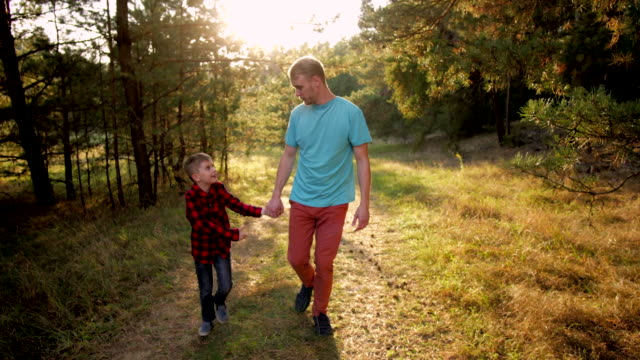 far och son gå i skogen - parent talking to child bildbanksvideor och videomaterial från bakom kulisserna