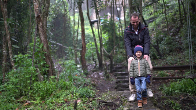Father and son walking carefully in the woods video