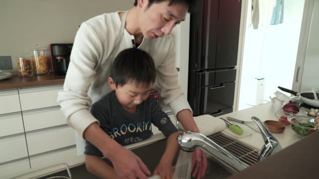 vidéos et rushes de père et fils se laver la vaisselle dans la cuisine ensemble - cuisine non professionnelle
