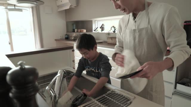 baba ve oğul birlikte mutfakta bulaşık - ev temizleme stok videoları ve detay görüntü çekimi