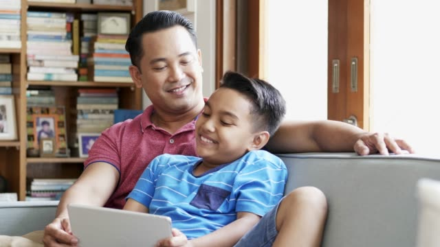 father and son watching digital tablet at home - etnia malese video stock e b–roll