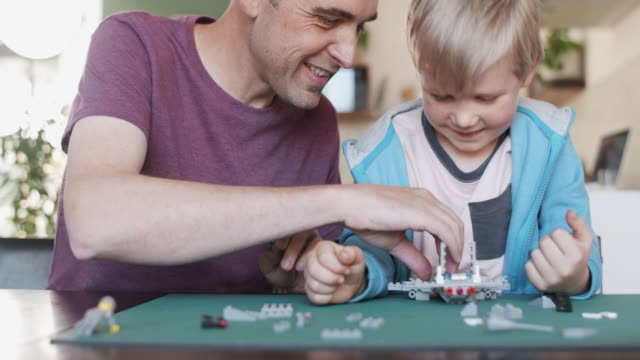 father and son with model aeroplane - puzzle video stock e b–roll