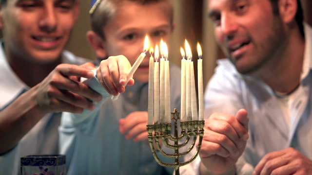 Father and sons lighting menorah video