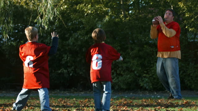 Father and sons playing football in Fall, slow motion video