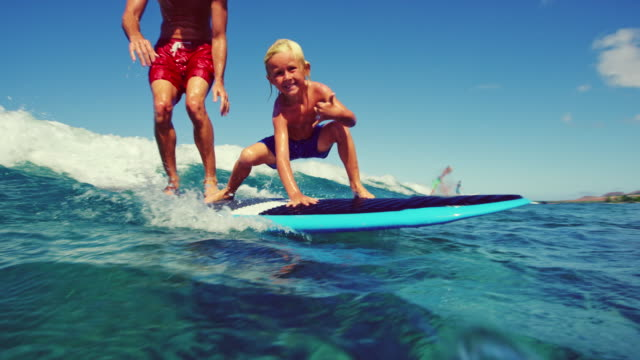 father and sun surfing - vacanze video stock e b–roll