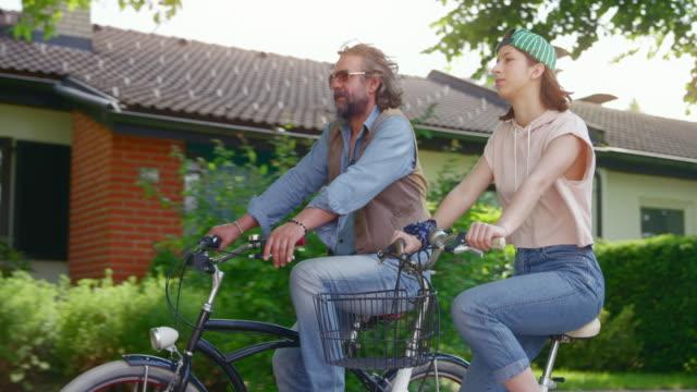 vidéos et rushes de slo mo ts père et fille adolescente conduisant leurs bicyclettes en bas de la rue ensoleillée - 18 19 ans