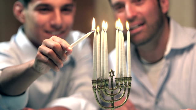 Father and teenage son lighting menorah video