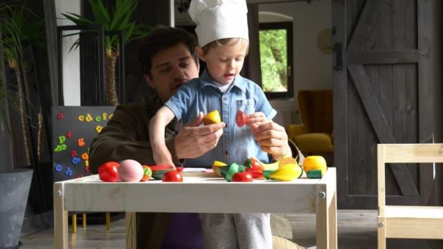 padre e bambino ragazzo in cappello chif giocare con verdure di plastica al coperto - giocattolo video stock e b–roll