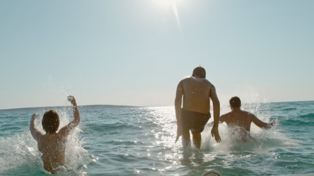 TIME WARP Father and two boys jumping into the sea from a pier
