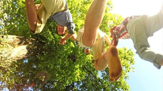 SLO MO Father and two sons jumping over the camera video