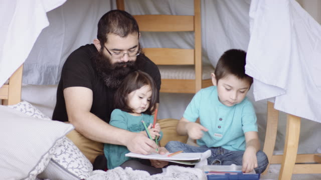 Father and young children reading book in fort Father and young children reading book in fort made of sheets and chairs fort stock videos & royalty-free footage