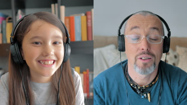 father and young daughter in multiscreen talk to disgruntled hearing aids - didattica a distanza video stock e b–roll