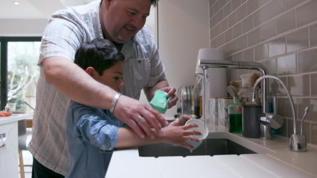 Father and young son washing up together at the kitchen sink