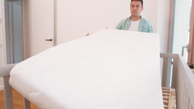 vídeos y material grabado en eventos de stock de padre arreglando cama de bebé con colchón en casa - colchón