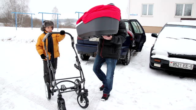 father assembles red baby stroller and son helps him. - 0 11 mesi video stock e b–roll