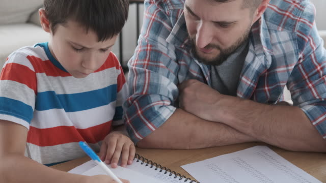 Father assisting son doing homework video