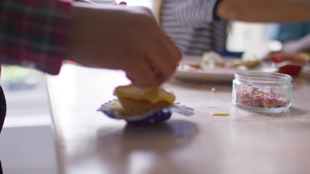 Father at home helping his children decorate biscuits