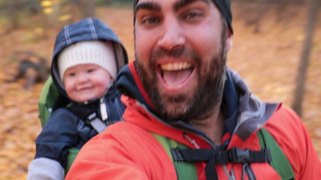 vídeos de stock e filmes b-roll de father backpacking hiking with baby in autumn forest - atividade recreativa