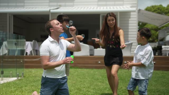 vídeos de stock, filmes e b-roll de pai, soprando bolhas com varinha de bolha ao ar livre - primavera estação do ano