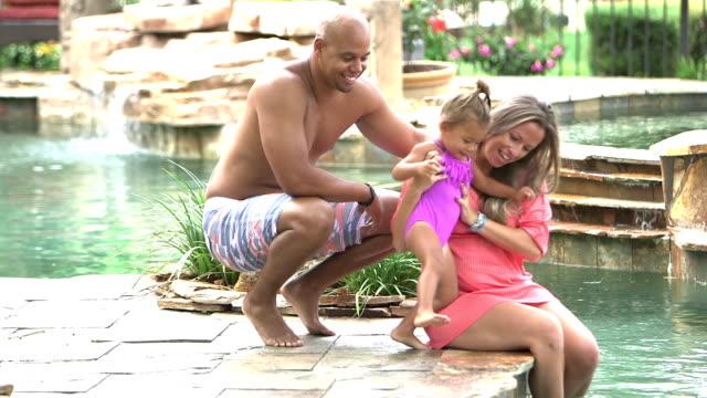 vidéos et rushes de père amène la petite fille de s'asseoir à côté de la mère à la piscine - 30 34 ans