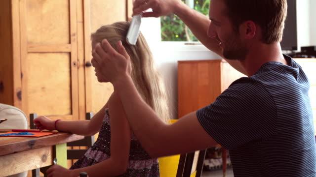 父と娘のヘアブラシを置くテーブルで履く ビデオ
